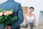 Businessman holding roses for colleague