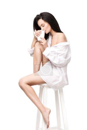 Photo pour Vue latérale de la femme, boire du café tout en étant assis sur la chaise isolé sur blanc - image libre de droit