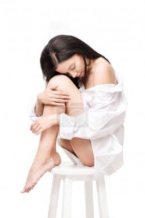 Photo pour Vue latérale d'une femme sensuelle assis sur chaise isolé sur blanc - image libre de droit