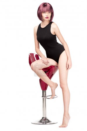 Woman in leotard posing on chair