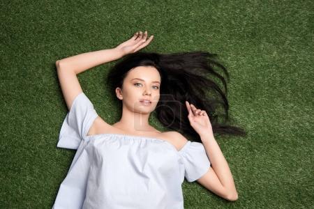 Foto de Arriba vista del atractivo joven mirando a cámara mientras se está acostado en la hierba - Imagen libre de derechos