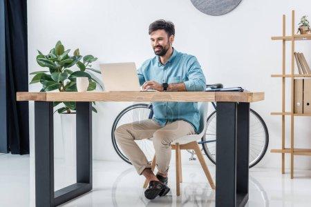 homme d'affaires avec ordinateur portable sur le lieu de travail