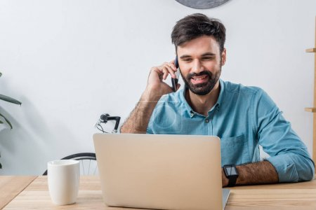 Photo for Portrait of smiling businessman talking on smartphone while looking at laptop at workplace - Royalty Free Image
