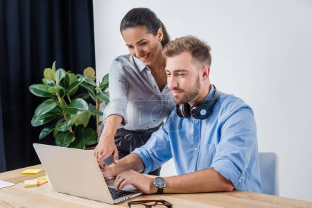 Photo for Portrait of businessman working on laptop with smiling colleague in office - Royalty Free Image