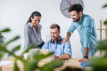 Photo for Group of young business colleagues working with laptop in office together - Royalty Free Image