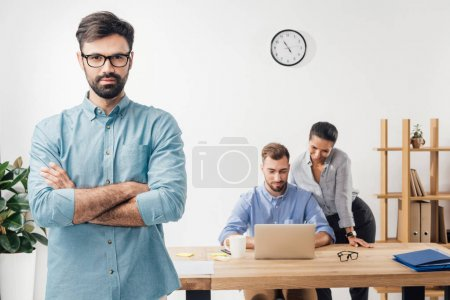 Photo for Businessman with crossed arms standing in office and colleagues working on laptop - Royalty Free Image