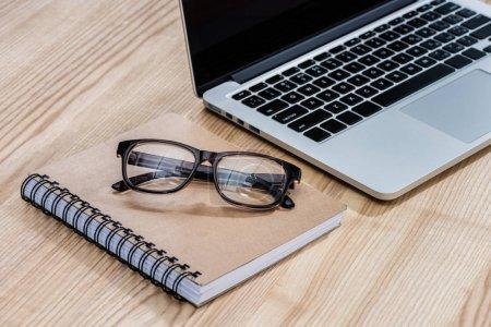 Photo pour Vue rapprochée de l'ordinateur portable, des lunettes et du portable sur une table en bois - image libre de droit