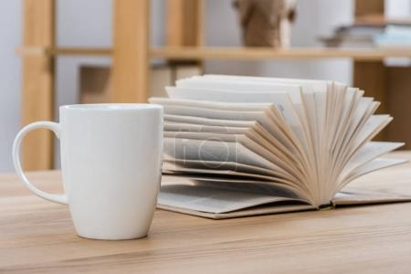 Photo for Close up view of cup of coffee and book on wooden table - Royalty Free Image