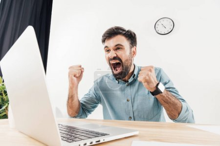 Photo for Portrait of excited businessman screaming and looking at laptop screen at workplace in office - Royalty Free Image