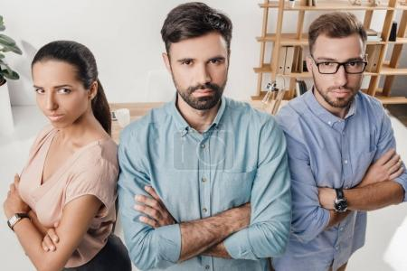 Photo for High angle view of serious business people with crossed arms standing at workplace in office - Royalty Free Image