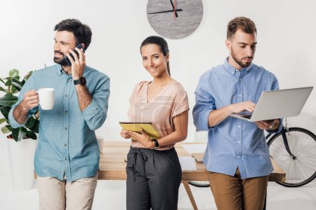 businesspeople with gadgets in office