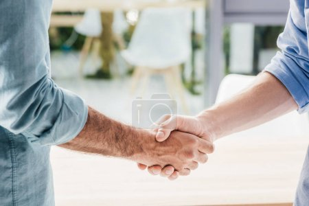 Cropped shot of businessmen shaking hands after meeting in office