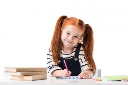 Photo pour Petite écolière rousse souriante dessinant dans un carnet avec des stylos en feutre et regardant la caméra isolée sur blanc - image libre de droit