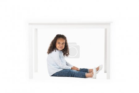african american girl sitting under table
