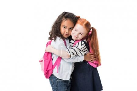 Photo for Adorable multiethnic schoolgirls with backpacks hugging isolated on white - Royalty Free Image