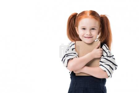 Photo for Adorable schoolgirl hugging book and smiling at camera isolated on white - Royalty Free Image