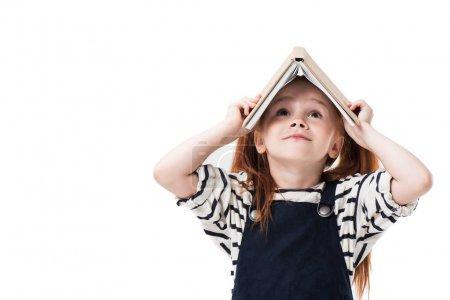 Photo pour Mignonne petite écolière rousse tenant livre au-dessus de la tête et regardant isolé sur blanc - image libre de droit