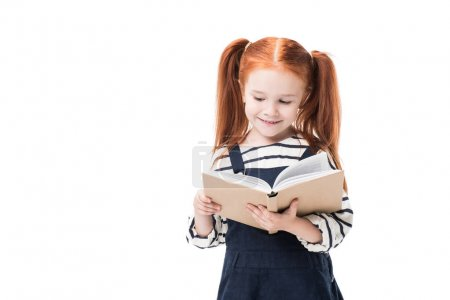Photo for Cute smiling elementary school student reading book isolated on white - Royalty Free Image