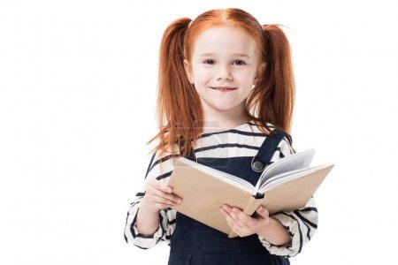 Photo pour Adorable petite écolière rousse tenant le livre et souriant à la caméra isolée sur blanc - image libre de droit