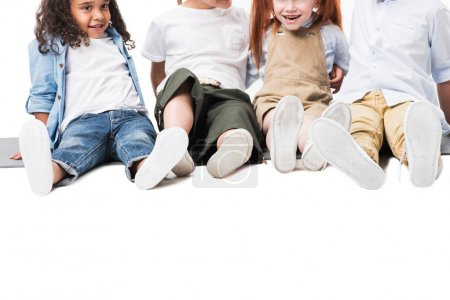 Photo pour Heureux enfants multiethniques assis ensemble isolé sur blanc - image libre de droit