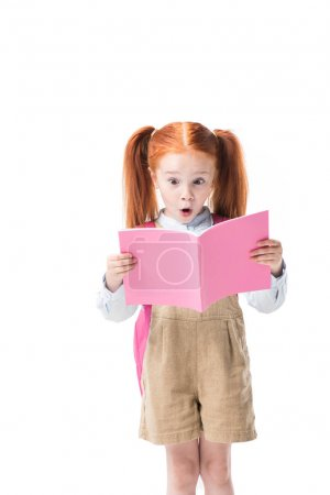 Photo for Adorable surprised redhead schoolgirl holding book isolated on white - Royalty Free Image