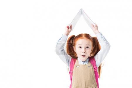 Photo pour Adorable écolière surprise tenant livre isolé sur blanc - image libre de droit