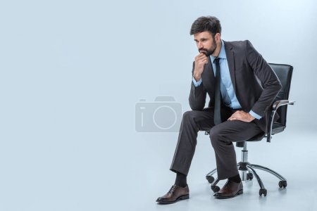 Photo for Pensive businessman sitting on chair and looking away isolated on blue - Royalty Free Image