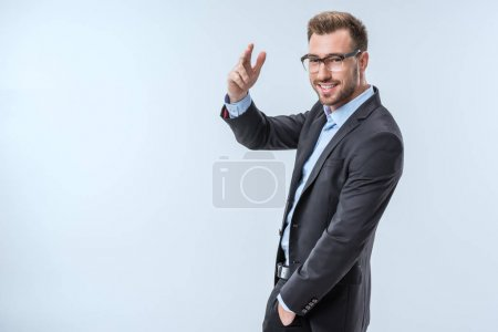 Photo for Side view of cheerful businessman in suit gesturing and looking at camera isolated on blue - Royalty Free Image