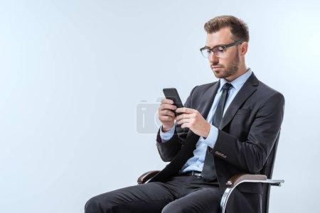 Photo pour Homme d'affaires ciblée en lunettes de vue à l'aide de smartphone isolé sur bleu - image libre de droit