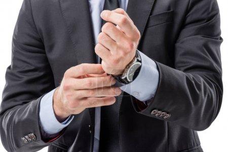 Photo pour Recadrée tir d'homme d'affaires en tenues boutonnage montre - image libre de droit