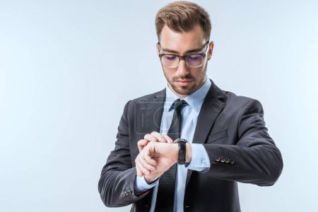 Photo pour Portrait de jeune homme d'affaires en lunettes vérifiant le temps sur montre isolé sur bleu - image libre de droit