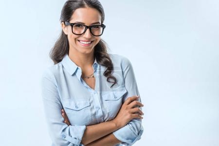 Photo for Portrait of smiling businesswoman in eyeglasses looking at camera isolated on blue - Royalty Free Image