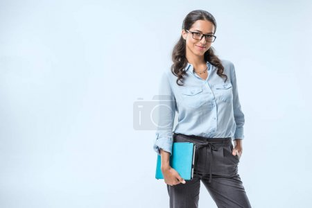 Photo for Portrait of smiling businesswoman in eyeglasses holding tablet in hand isolated on blue - Royalty Free Image