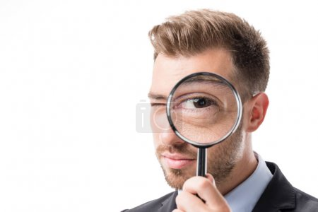 Photo for Portrait of businessman looking at camera through magnifying glass isolated on white - Royalty Free Image