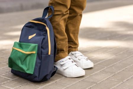 Photo pour Recadrée tir d'écolier élégant permanent avec sac à dos sur la rue - image libre de droit