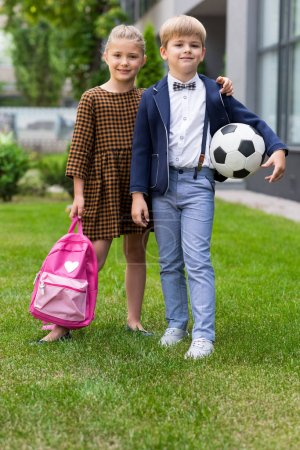 Schoolkids with backpack and soccer ball
