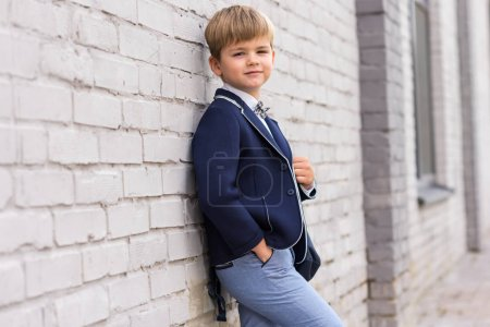 stylish boy leaning at wall