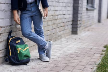 Photo pour Recadrée tir d'écolier élégant avec sac à dos tient livre en se tenant debout sur la rue - image libre de droit