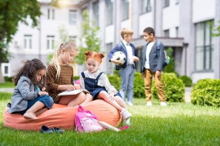 Photo for Adorable multiethnic schoolgirls sitting on bean bag chair and reading book while schoolboys standing with soccer ball on schoolyard - Royalty Free Image