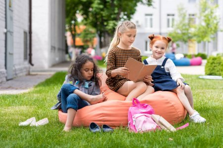 Photo for Adorable multiethnic schoolgirls sitting on bean bag chair and reading book on schoolyard - Royalty Free Image