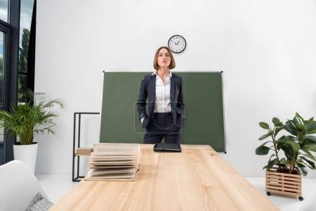 Photo pour Jeune enseignante confiante debout avec les mains dans les poches en classe - image libre de droit