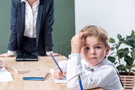 schoolboy with teacher in classroom