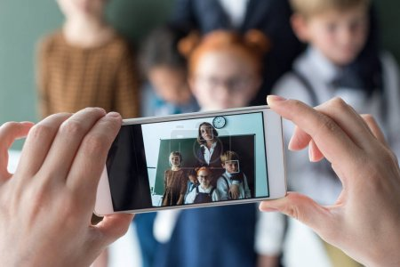 Teacher and students photographing with smartphone