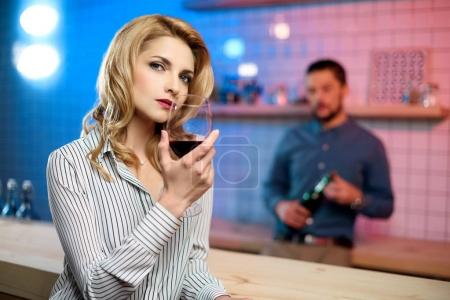 woman drinking wine in bar