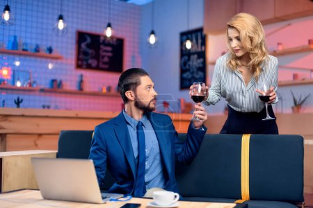 Photo for Beautiful young woman giving wine glass to handsome bearded man using laptop in restaurant - Royalty Free Image