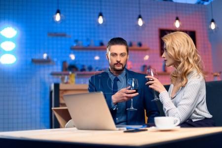 Photo pour Barbu élégant homme et jeune femme blonde, boire du vin tout en utilisant le portable de restaurant - image libre de droit