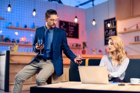 Photo for Handsome bearded man bringing wine to young beautiful woman using laptop in bar - Royalty Free Image