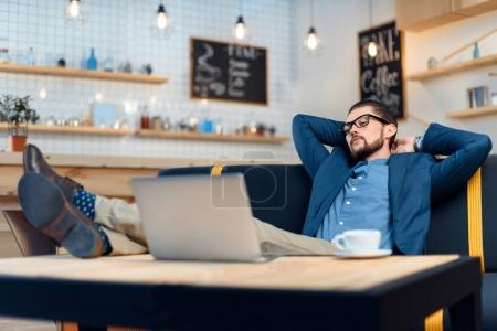Photo for Relaxed young buisnessman in eyeglasses looking at laptop while sitting and working in cafe - Royalty Free Image