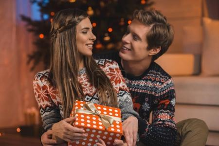 man hugging girlfriend with christmas present