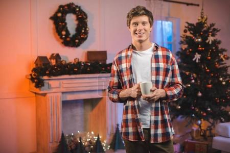 Photo for Portrait of smiling man with cup of hot drink looking at camera in christmas decorated room - Royalty Free Image